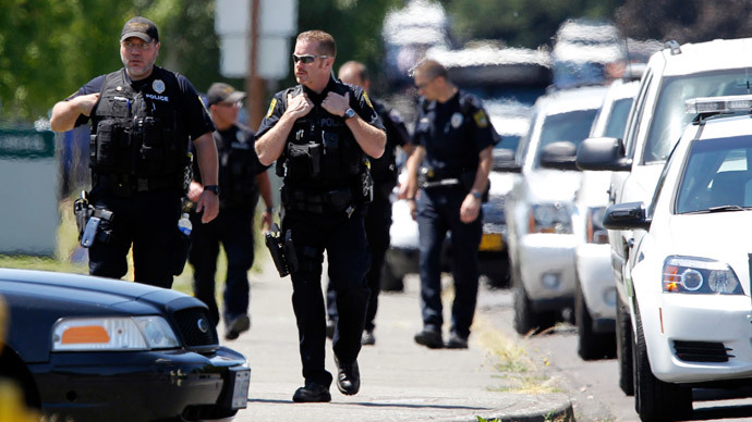 Police officers stand on the sidewalk after a shooting at Reynolds High School in Troutdale, Oregon June 10, 2014.(Reuters / Steve Dipaola)