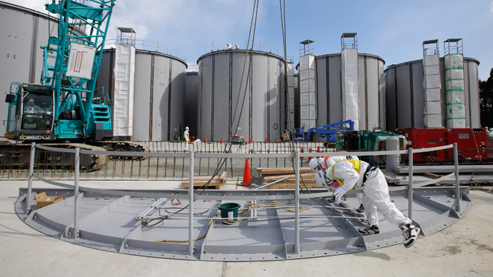 Men wearing protective suits and masks work in front of welding storage tanks for radioactive water, under construction in the J1 area at the Tokyo Electric Power Co's (TEPCO) tsunami-crippled Fukushima Daiichi nuclear power plant in Okuma in Fukushima prefecture (AFP Photo / POOL)