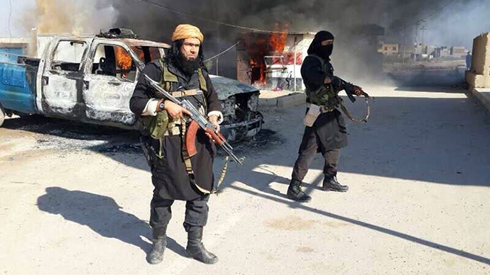 Shakir Wahib (L), Abu Wahib, a leader of the Islamic State of Iraq and the Levant (ISIL) standing next to burning cars, at an undisclosed location in Iraq (AFP Photo / HO)