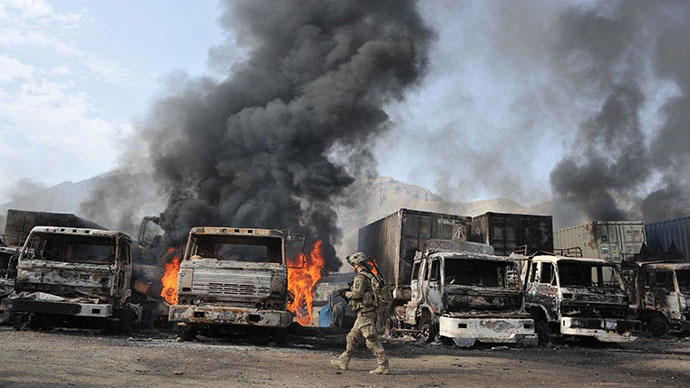 A US soldier walks past burning trucks at the scene of a suicide attack at the Afghan-Pakistan border crossing in Torkham, Nangarhar province on June 19, 2014. (Reuters / Noorullah Shirzada)