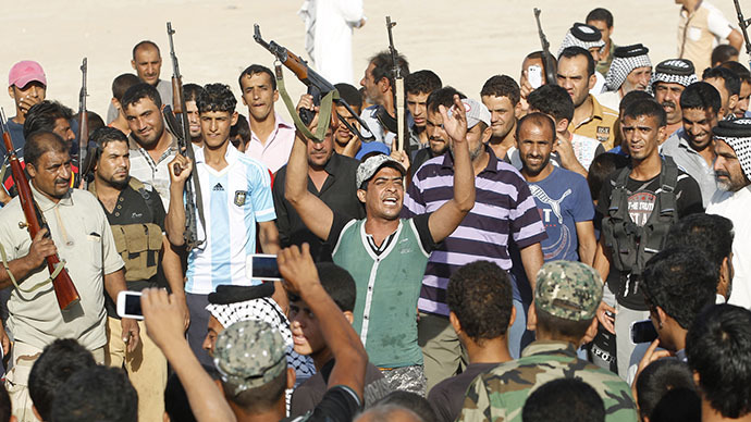 Volunteers, who have joined the Iraqi Army to fight against predominantly Sunni militants from the radical Islamic State of Iraq and the Levant (ISIL), gather with their weapons during a parade in the streets in Al-Fdhiliya district, eastern Baghdad June 15, 2014. (Reuters / Thaier Al-Sudani)