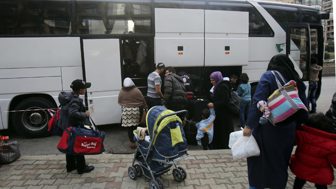 Syrian refugees load their luggage as they head to board a bus to be transported to Beirut international airport for resettlement in Germany, in Beirut April 15, 2014. (Reuters)