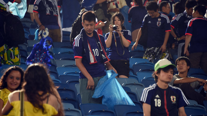 Japanese fan clean the tribune after a Group C football match between Japan and Greece at the Dunas Arena in Natal during the 2014 FIFA World Cup on June 19, 2014. (AFP Photo / Toshifumi Kitamura)