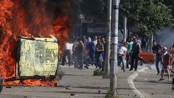 Kosovo Albanian demonstrators throw rocks towards the police, while standing near a burning vehicle set on fire during a protest in the ethnically divided town of Mitrovica June 22, 2014. (Reuters / Hazir Reka)