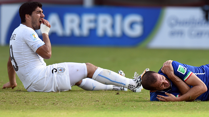 Uruguay's forward Luis Suarez (L) reacts past Italy's defender Giorgio Chiellini during a Group D football match between Italy and Uruguay at the Dunas Arena in Natal during the 2014 FIFA World Cup on June 24, 2014. (AFP Photo / Javier Soriano)