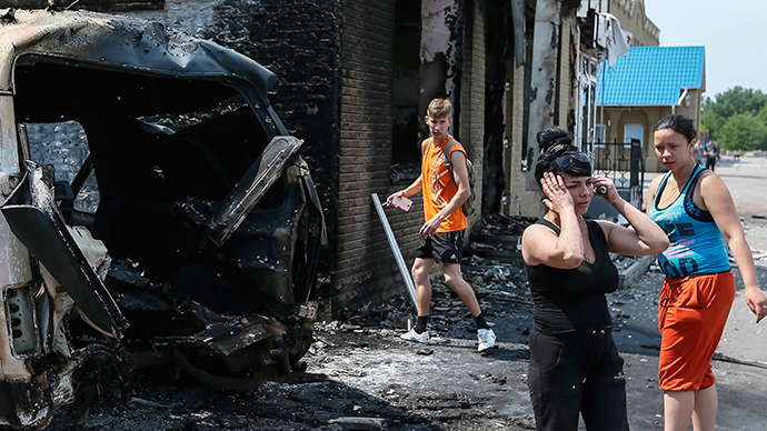 Local residents react as they stand near destroyed houses and vehicles after what locals say was overnight shelling by Ukrainian forces, in the eastern Ukrainian town of Slavyansk June 9, 2014 (Reuters / Gleb Garanich)
