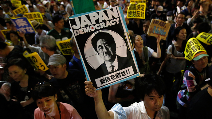 Protesters holding placards shout slogans at a rally against Japan's Prime Minister Shinzo Abe's push to expand Japan's military role in front of Abe's official residence in Tokyo June 30, 2014 (Reuters / Yuya Shino)