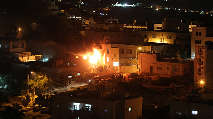 Flames and smoke billow from the blown-up house of Amer Abu Eisheh, one of two Palestinians suspected in the killing of three kidnapped Israelis, in the West Bank town of Hebron on July 1,2014 (AFP Photo / Hazem Bader)