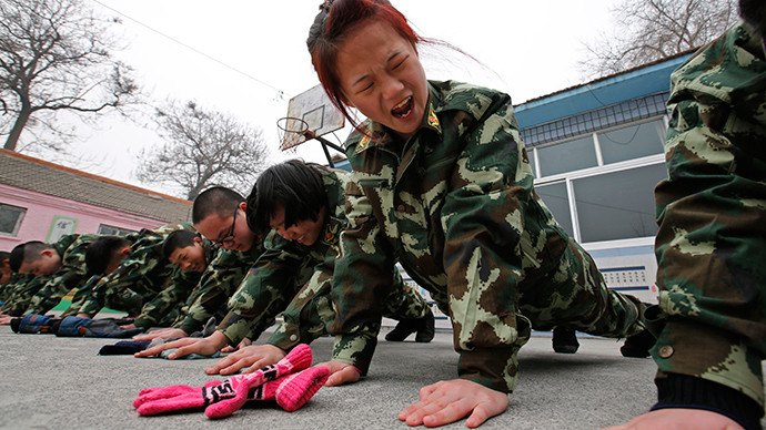 Students receive a group punishment during a military-style close-order drill class at the Qide Education Center in Beijing February 19, 2014 (Reuters / Kim Kyung-Hoon)