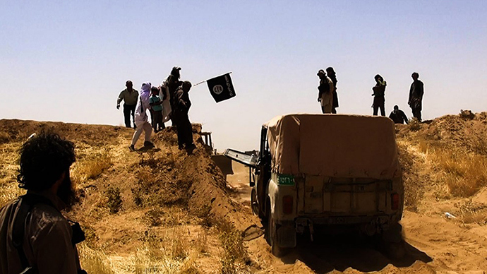 File image: Islamic State of Iraq and the Levant (ISIL) militants waving the trademark Jihadits flag as vehicles drive on a newly cut road through the Syrian-Iraqi border between the Iraqi Nineveh province and the Syrian town of Al-Hasakah (AFP Photo)