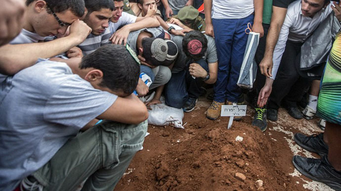 Relatives and friends gather around a grave, as Gilad Shaer, 16, Naftali Frenkel, 16, and Eyal Ifrach, 19, are buried side-by-side in the central Israeli town of Modiin on July 1, 2014. (AFP Photo / Jack Guez)