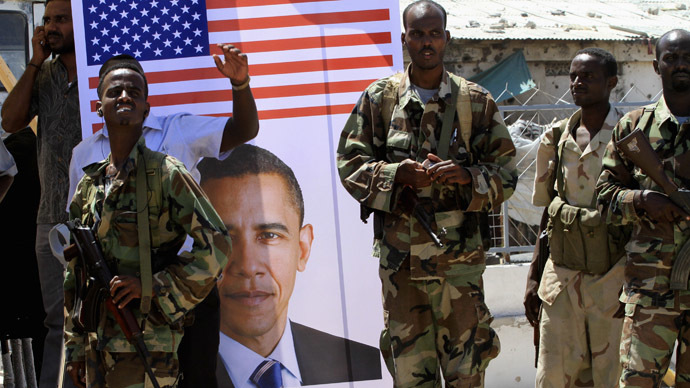 Somali soldiers stand next to a poster of U.S President Barack Obama during a rally welcoming the announcement that the United States has officially recognized Somalia's government, after more than two decades, in Mogadishu January 21, 2013. (Reuters/Omar Faruk)