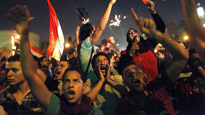 Egyptian protesters calling for the ouster of President Mohamed Morsi react as they watch his speech on a screen in a street leading to presidential palace early in Cairo on July 3, 2013. (AFP Photo / Mahmoud Khaled)