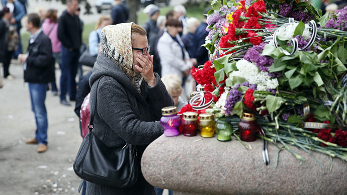 A woman reacts as she stands near flowers and lit candles placed in memory of people killed in recent street battles between pro-Russian and pro-Ukrainian supporters, outside a trade union building in the Black Sea port of Odessa, May 4, 2014. (Reuters / Gleb Garanich)