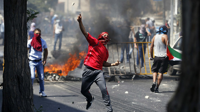 A Palestinian throws a stone during clashes with Israeli police after prayers on the first Friday of the holy month of Ramadan in the East Jerusalem neighbourhood of Wadi al-Joz July 4, 2014. (Reuters/Baz Ratner)
