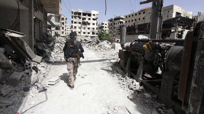 A Free Syrian Army fighter walks past debris of damaged buildings in the Ain Tarma neighbourhood of Damascus June 3, 2014. (Reuters/Badra Mamet)