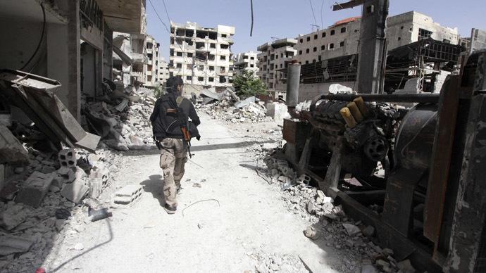 A Free Syrian Army fighter walks past debris of damaged buildings in the Ain Tarma neighbourhood of Damascus June 3, 2014. (Reuters/Badra Mamet)