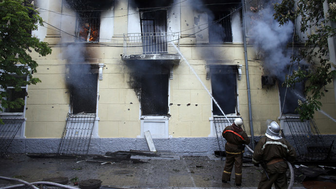 Firefighters extinguish a fire at the police HQ in the southeastern port city of Mariupol on May 9, 2014 after Kiev's tanks fired shells at it. (Reuters/Marko Djurica)