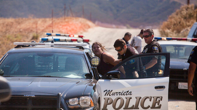 A protester is handcuffed and placed in a police car after a scuffle broke out before the possible arrivals of undocumented migrants who may be processed at the Murrieta Border Patrol Station in Murrieta, California July 4, 2014.(Reuters / Sam Hodgson)