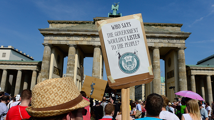 Demonstrators hold up banners as they take part in a protest in front of Berlin's landmark Brandenburg Gate against the US National Security Agency (NSA) collecting German emails, online chats and phone calls and sharing some of it with the country's intelligence services in Berlin (AFP Photo)