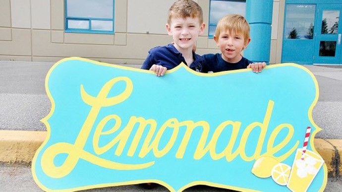 Quinn Callender (L) and Brayden Grozdanich (R) pose by their lemonade stand outside a grocery store in Pitt Meadows, B.C. Photo from youcaring.com