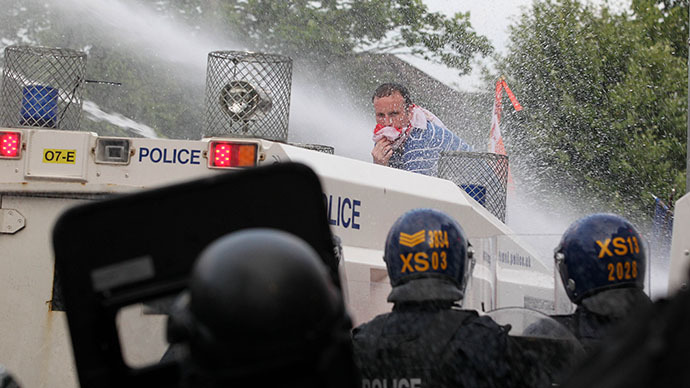 An Orangemen protester stands on a police vehicle as police use water cannon during clashes on the return from a march in north Belfast, Northern Ireland, on July 12, 2013. (AFP Photo / Peter Muhly)