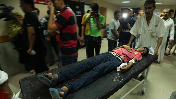 A wounded Palestinian boy, who hospital officials said was injured in an Israeli air strike, is wheeled into a hospital in Gaza City July 12, 2014. (Reuters / Mohammed Salem)