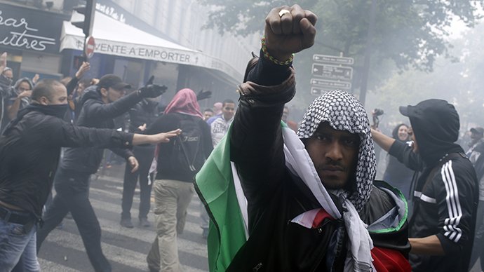 A protester wearing a kaffiyeh and wrapped in a Palestinian flag raises his fist on July 13, 2014 in Paris. (AFP Photo / Kenzo Tribouillard)