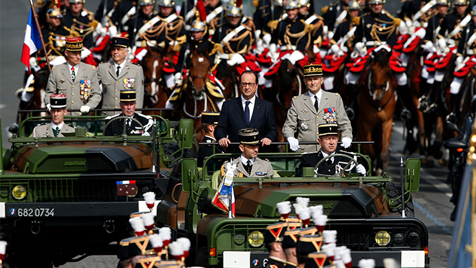 France's President Francois Hollande (L) and French Army Chief of Staff, General Pierre de Villiers ride in a command car during the traditional Bastille Day parade on the Champs Elysees in Paris July 14, 2014 (Reuters / Benoit Tessier)