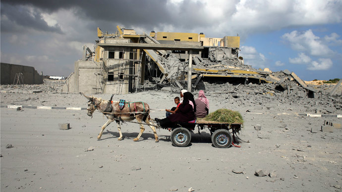 Palestinians ride a donkey cart past a police station, which was under construction when it was destroyed in what police said was an Israeli air strike in Rafah in the southern Gaza Strip July 15, 2014. (Reuters / Ibraheem Abu Mustafa)