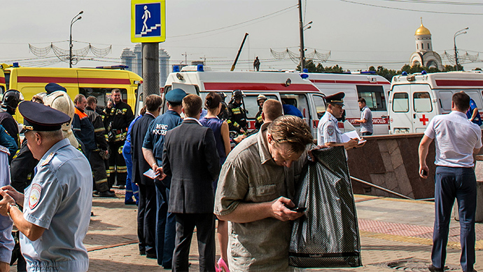 Police officers and rescuers crowd near an entrance to the Park Pobedy metro station close to the site of a metro accident in Moscow, on July 15, 2014 (AFP Photo / Dmitry Serebryakov)