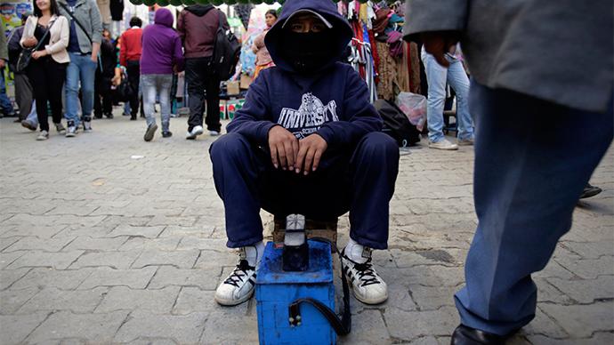 A boy working as a shoe shiner is seen in La Paz (Reuters / David Mercado)