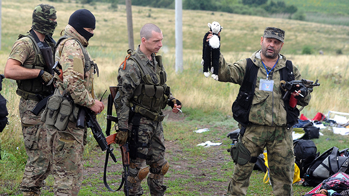 A member of the  self-defense forces holds up a stuffed animal as others look on at the site of the crash of a Malaysian airliner carrying 298 people from Amsterdam to Kuala Lumpur in Grabove, in east Ukraine, on July 18, 2014. (AFP Photo / Dominique Faget)