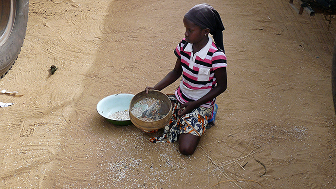 A girl gathers rice spilled from a humanitarian food convoy that arrived from the Malian capital Bamako in the northeastern city of Gao (Reuters / Adama Diarra)