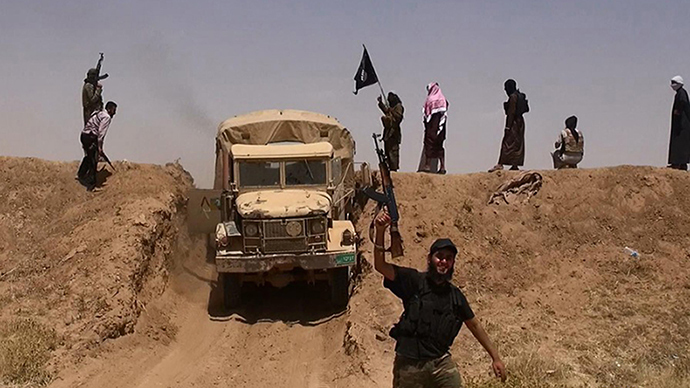 An image made available by the jihadist Twitter account Al-Baraka news on June 11, 2014 allegedly shows militants of the jihadist group Islamic State of Iraq and the Levant (ISIL) waving the Islamic Jihad flag and holding up their weapons as a vehicle drives on a newly cut road through the Syrian-Iraqi border between the Iraqi Nineveh province and the Syrian town of Al-Hasakah (AFP Photo / HO)