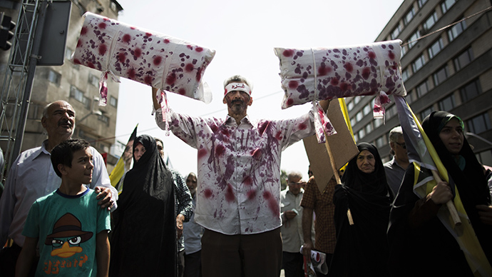 "An Iranian man wears a blood stained shirt with a headband bearing the word ""Gaza"" during a demonstration in Tehran on July 25, 2014 to mark Quds (Jerusalem) Day. (AFP Photo / Behrouz Mehri)"