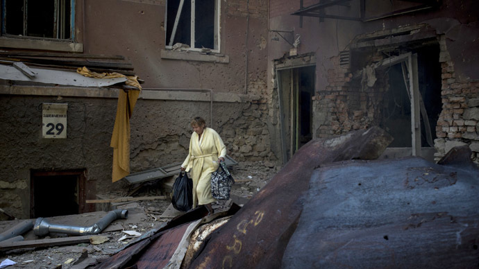 A woman is seen outside a residential building destroyed in an artillery attack by the Ukrainian army on Lugansk. (RIA Novosti/Valeriy Melnikov)