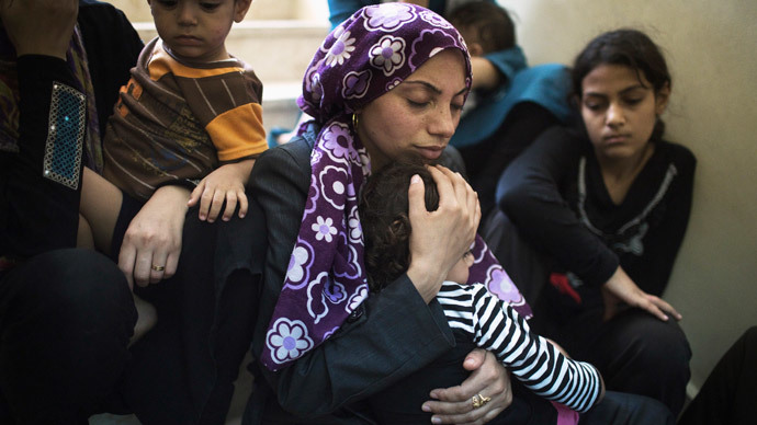 A Palestinian mother comforts her child in a hospital a few hundred meters from where medics said Israeli shelling hit a U.N-run school sheltering Palestinian refugees, in Beit Hanoun the northern Gaza Strip July 24, 2014.(Reuters / Finbarr O'Reilly)
