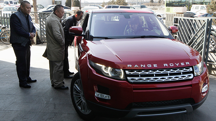 Customers look at a Range Rover Evoque car outside a dealership in Beijing (Reuters / Jason Lee)