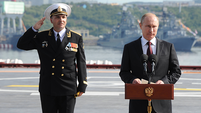 Russian President Vladimir Putin, right, is seen on board the Admiral Kuznetsov aircraft carrier congratulating mariners before the parade and the staged performance by combat ships of Russia's Northern Fleet, July 27, 2014 (RIA Novosti / Michael Klimentyev)