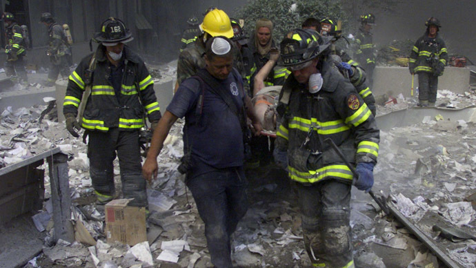 Firemen carry an injured man from the World Trade Center after both towers collapsed after planes crashed into the buildings in New York on September 11, 2001. (Reuters/Peter Morgan)