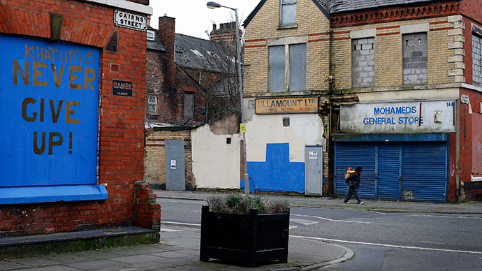 A woman carries a child on her back past boarded up property in the Granby Street area in Liverpool, northern England (Reuters / Phil Noble)
