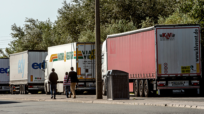 Migrants walk past lorries in Calais, northern France, on August 5, 2014 (AFP Photo / Pilippe Huguen)
