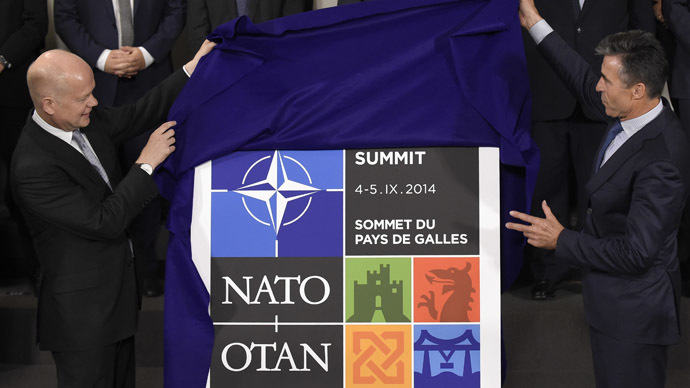 British Foreign Secretary of State for Foreign an Commonwealth Affairs, William Hague (L) and NATO Secretary General Anders Fogh Rasmussen unveils the logo of the NATO Wales' summit before a family picture as part of a Foreign Affairs Ministers meeting in Brussels on June 25, 2014. (AFP Photo)