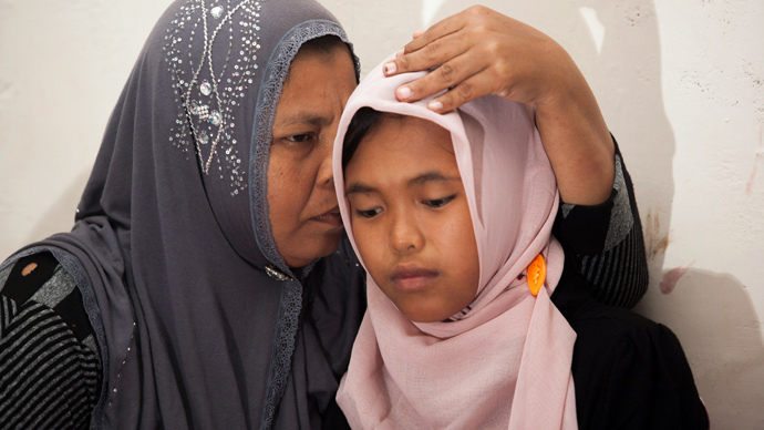 Indonesian mother Jamaliah (L) hugs her daughter Raudhatul Jannah (R) after they were reunited in Meulaboh, Aceh province on August 7, 2014.  (AFP Photo / Chaideer Mahyuddin)