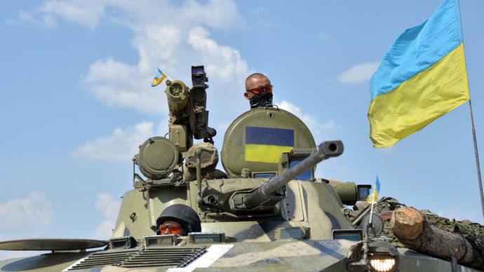 Ukrainian servicemen sit on an armoured vehicle with a Ukrainian flag as a convoy of Ukrainian forces drive towards the eastern city of Debaltceve, in the region of Donetsk, on July 30, 2014. (AFP Photo/Genya Savilov)