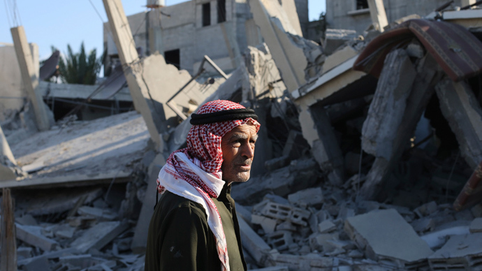 A Palestinian man stands next to the remains of a house, which witnesses said was destroyed in an Israeli air strike, in Rafah in the southern Gaza Strip August 10, 2014 (Reuters / Ibraheem Abu Mustafa)