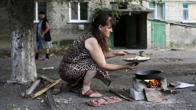 A woman cooks over a campfire due to gas cuts in her building on August 3, 2014 in eastern Ukrainian city of Popasna, Lugansk region (AFP Photo)