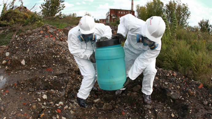 Employees of Ukrainian Emergency Ministry carry a barrel containing highly toxic waste during the removal of waste containers from the former Soviet military chemical plant in Gorlovka, an industrial city in the Donetsk region. (AFP Photo / Alexander Khudoteply)