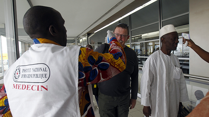 Health workers take passengers' temperatures infrared digital laser thermometers at the Felix Houphouet Boigny international airport in Abidjan August 13, 2014. (Reuters / Luc Gnago)